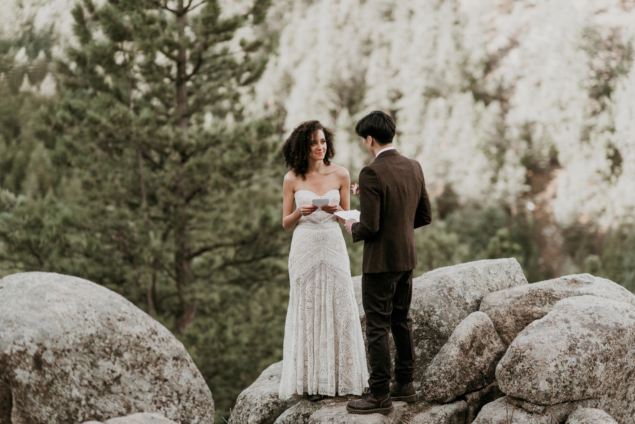 Reading vows on a mountain at sunrise, the bride is wearing rue de seine and the groom is in a dark brown wool tweed suit.