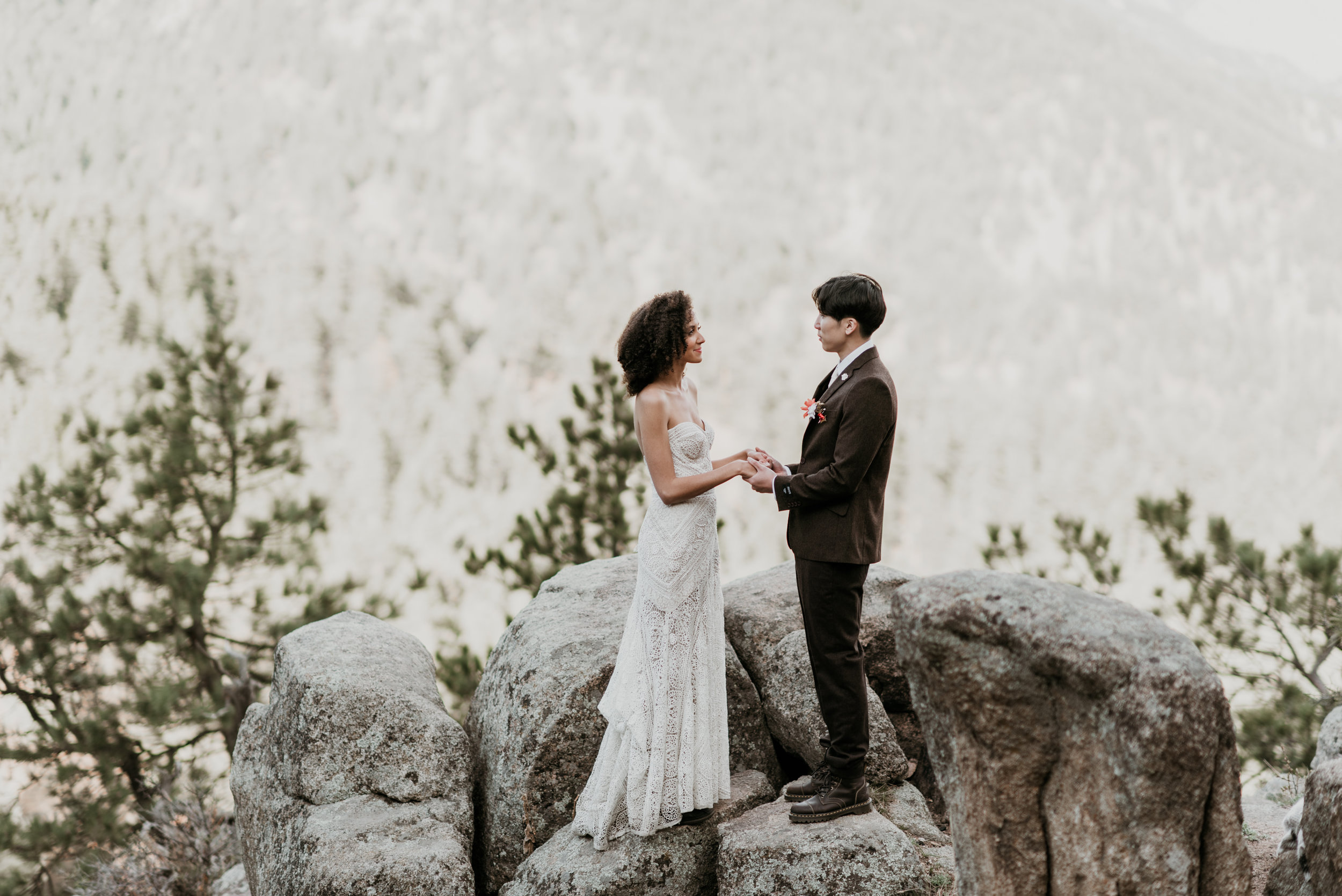 The bride and groom hold hands on a mountain overlooking the Colorado foothills in Boulder.