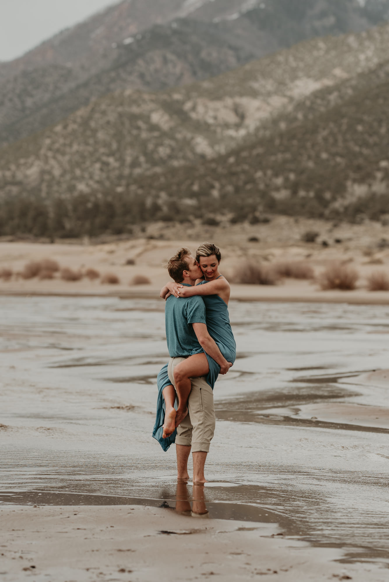 A romantic summer engagement photo showing the Sangre de Cristo Range in the background.