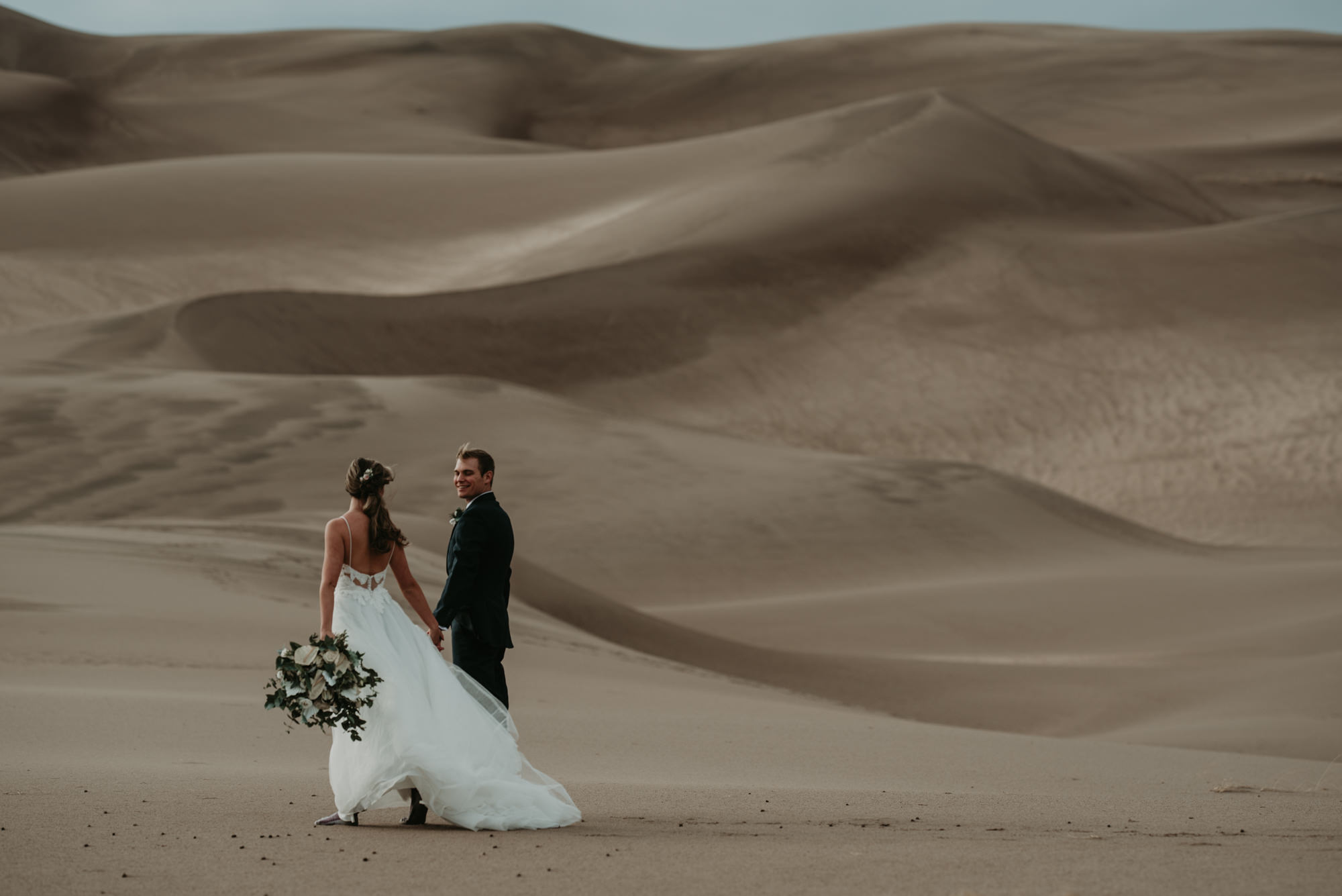 Brittany and Eric hold hands during their sand dunes elopement