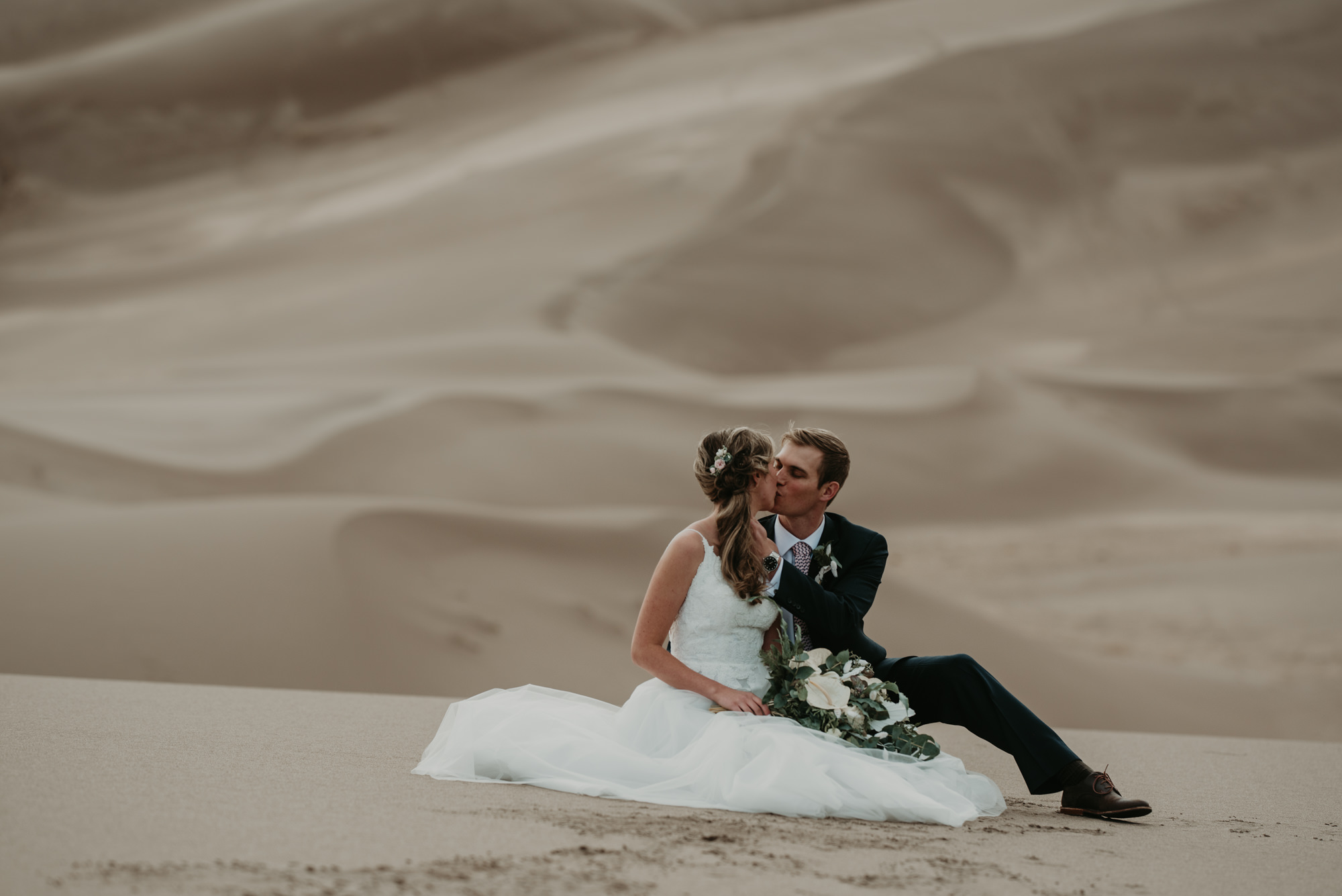 The bride and groom share a kiss on the sand dunes.