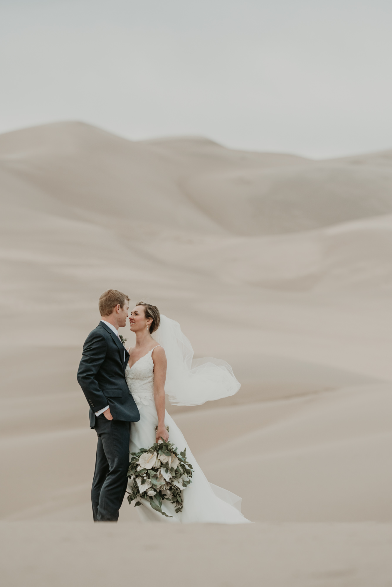 Brittany and Eric share a kiss with the Great Sand Dunes rising up behind them.
