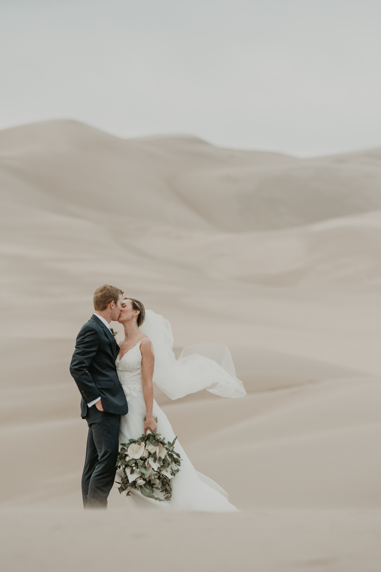 Brittany and Eric share a kiss with the Sand Dunes in the background.