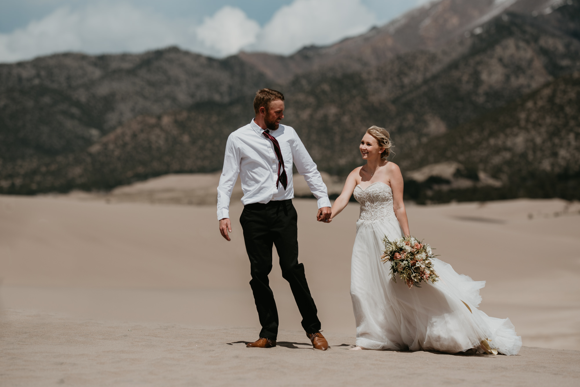 Doug and Kaitlyn walk hand in hand across the sand dunes.