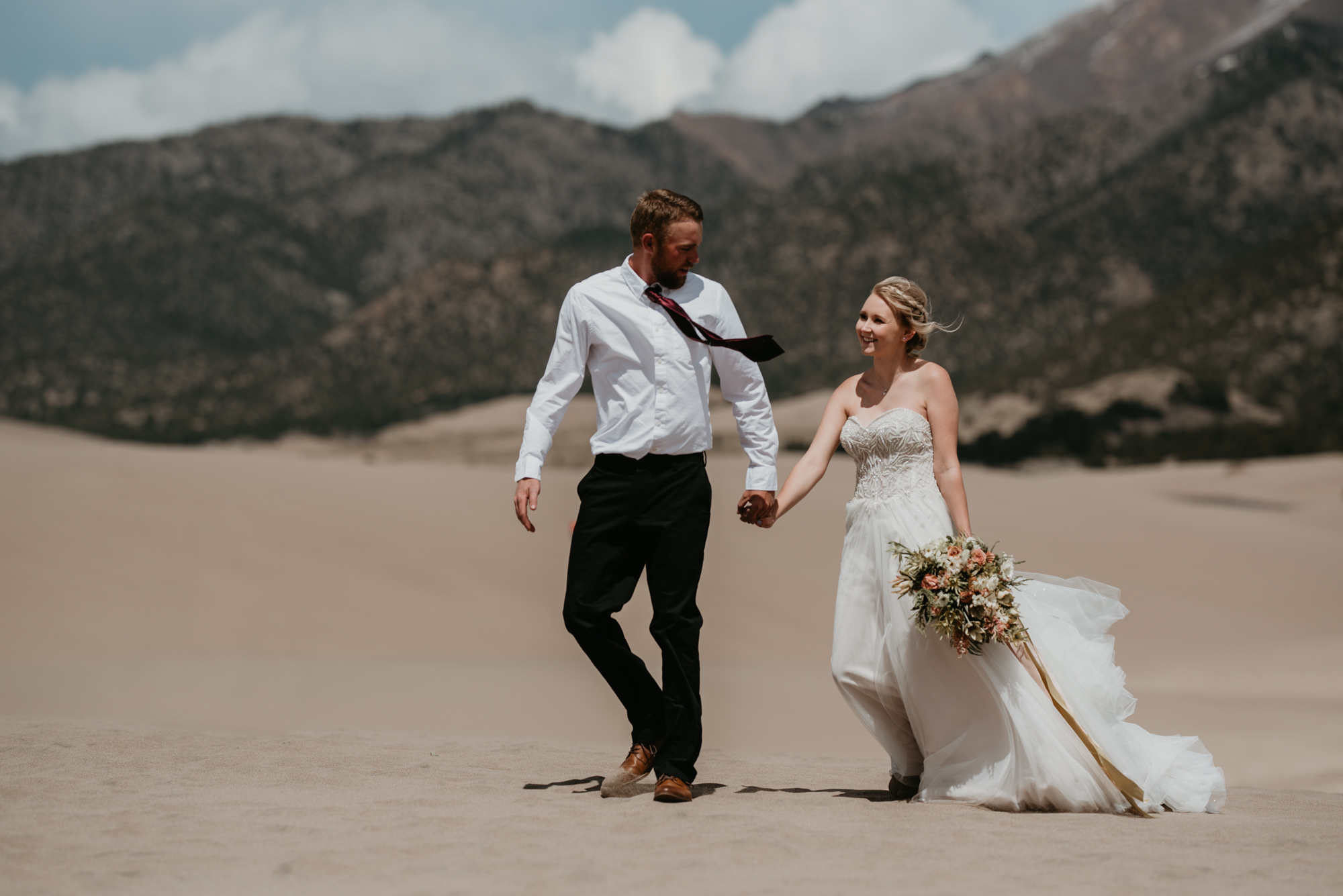 Doug and Kaitlyn walk hand in hand across the sand dunes in Southern Colorado.