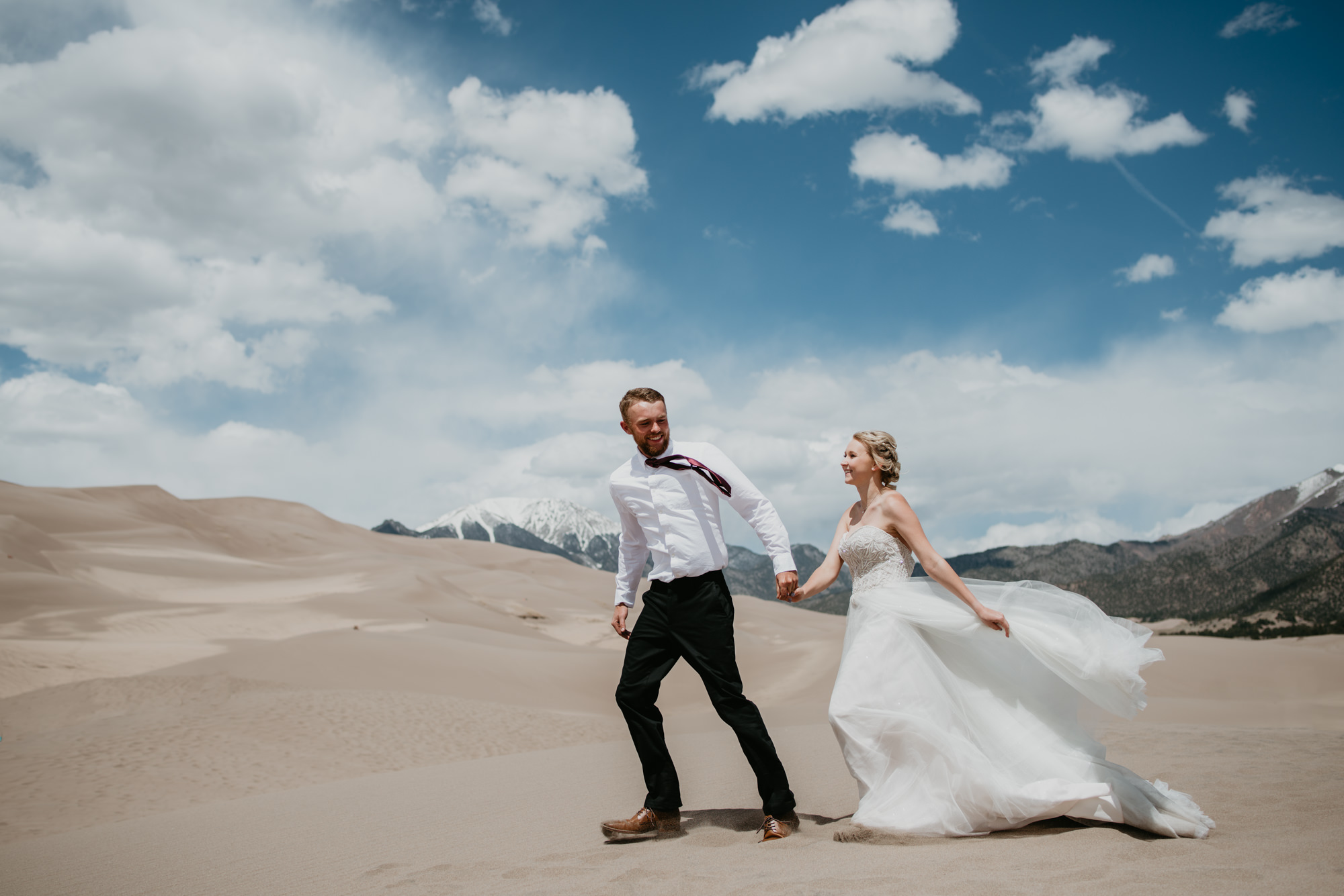 Bride and Groom walk hand in hand beneath bluebird skies.