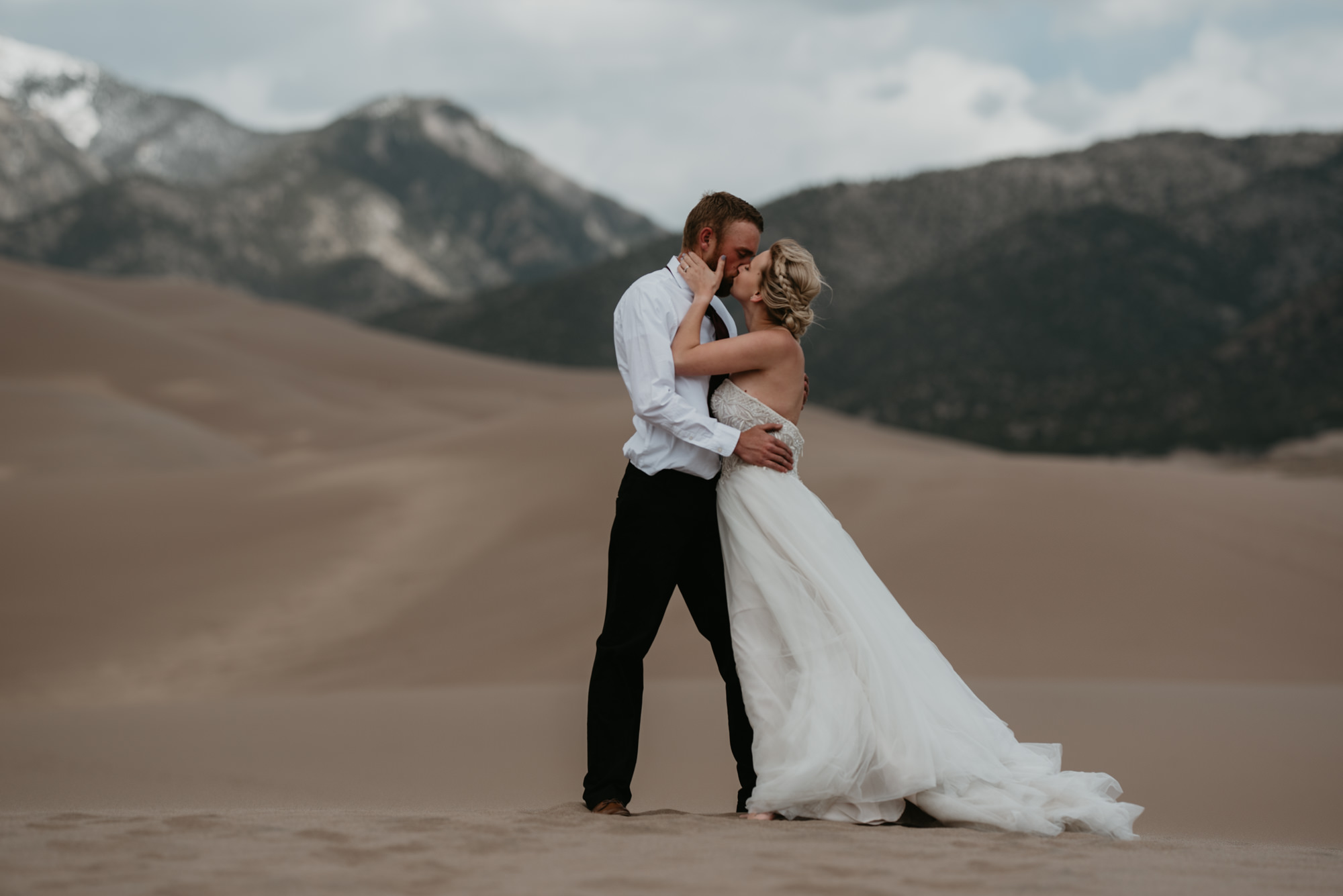 The bride and groom kiss passionately in front of Colorado mountains.