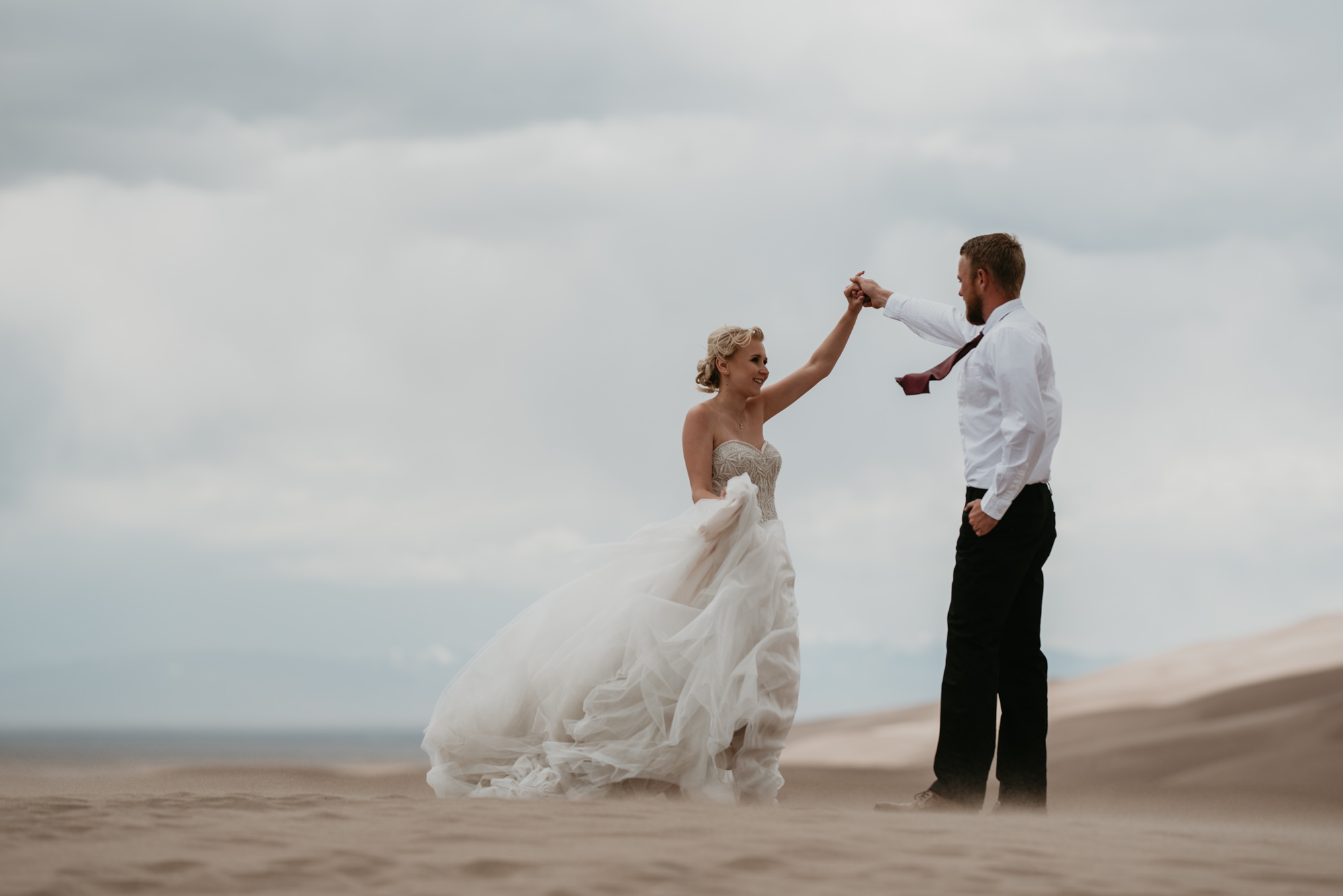 Kaitlyn and Doug dance in the sand under overcast skies.