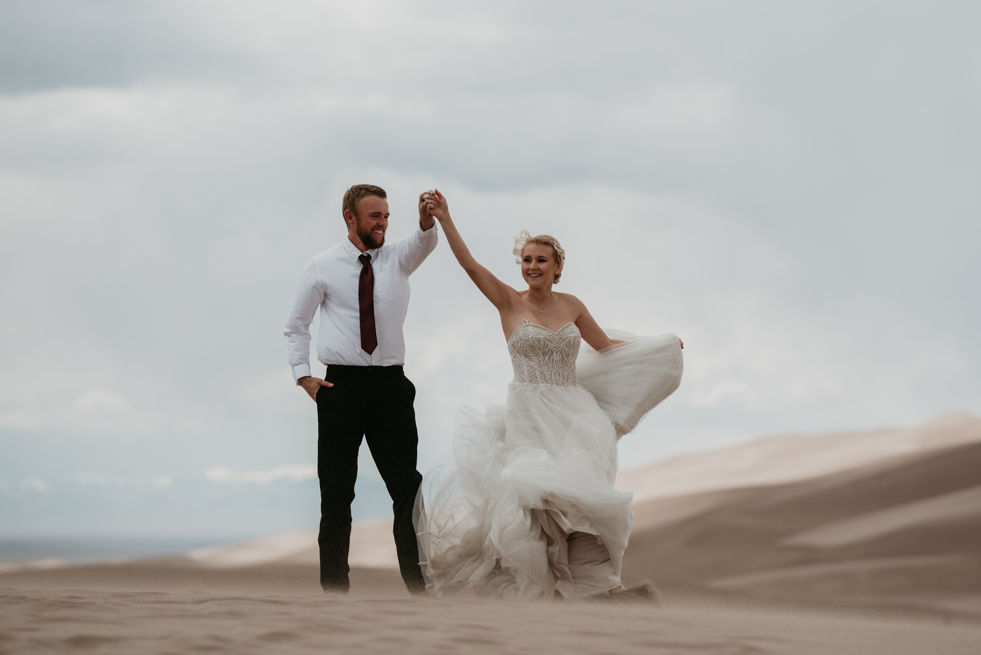 The bride and groom dance under overcast skies.