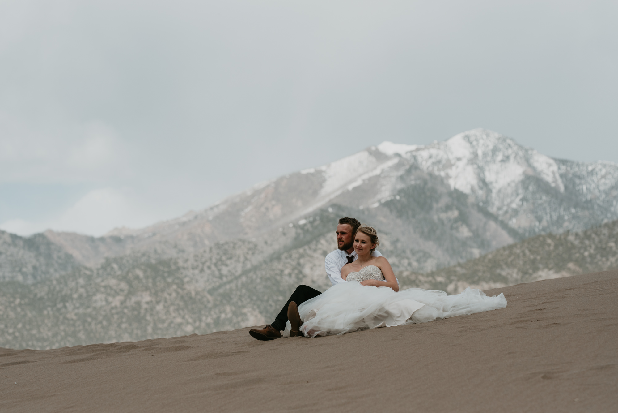 Bride and groom hold each other while sitting on the dunes in front of the Sangre de Cristo mountain range.