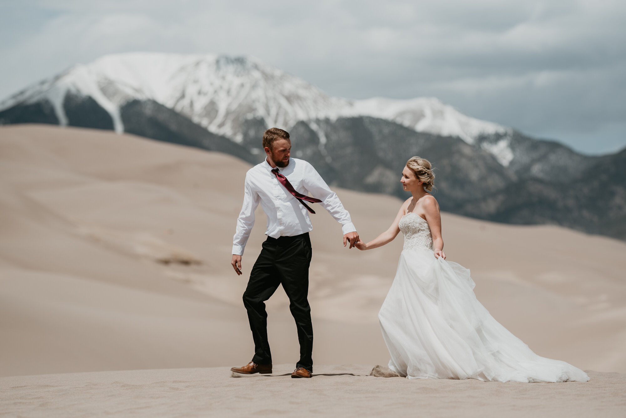 Eloping couple Kaitlyn and Doug walk hand in hand on sweeping sand dunes with snow capped mountains in the background.