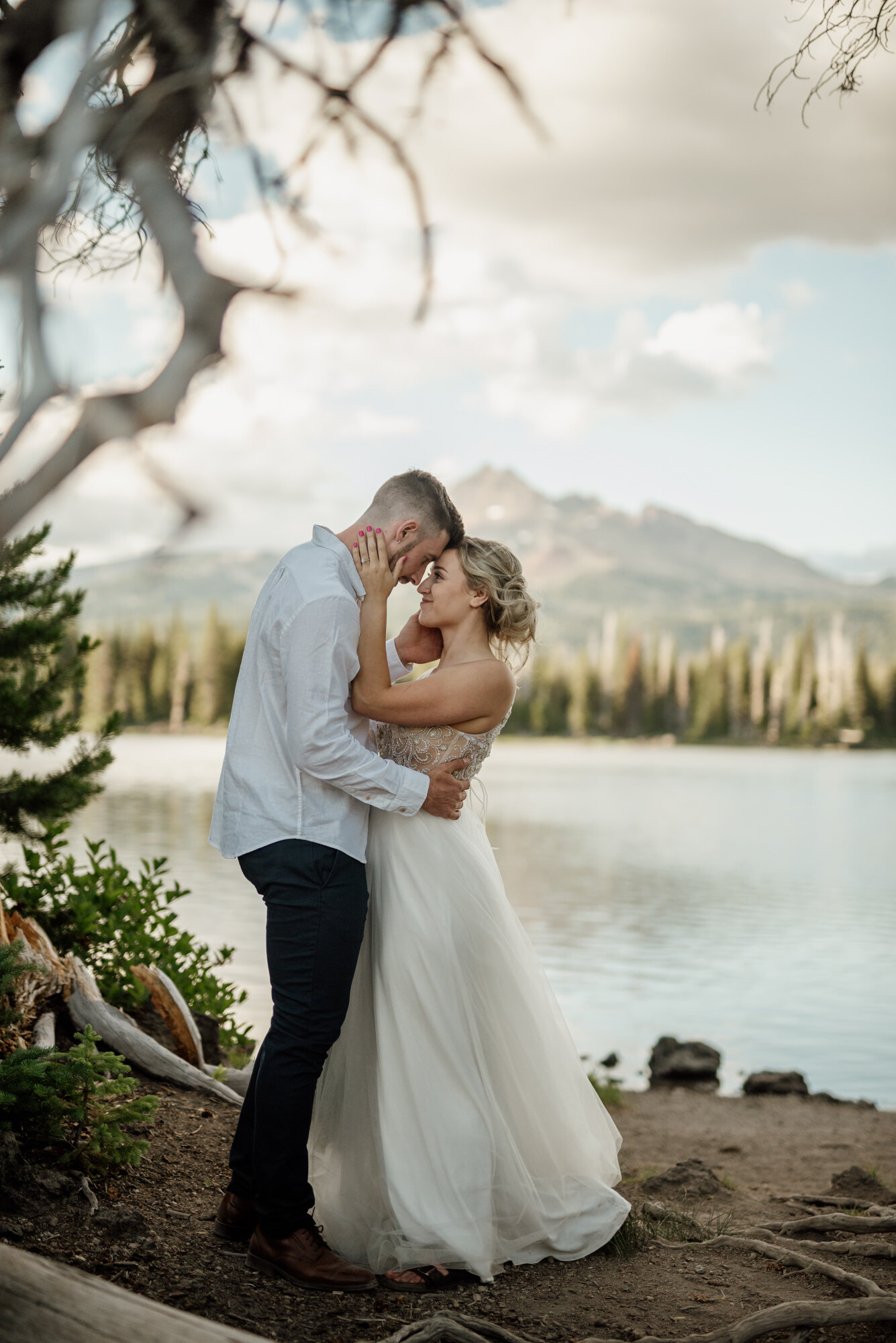 Aaron and Taryn embrace on their wedding day in front of a dormant volcano in eastern Oregon. Sunset lights up the trees behind them.