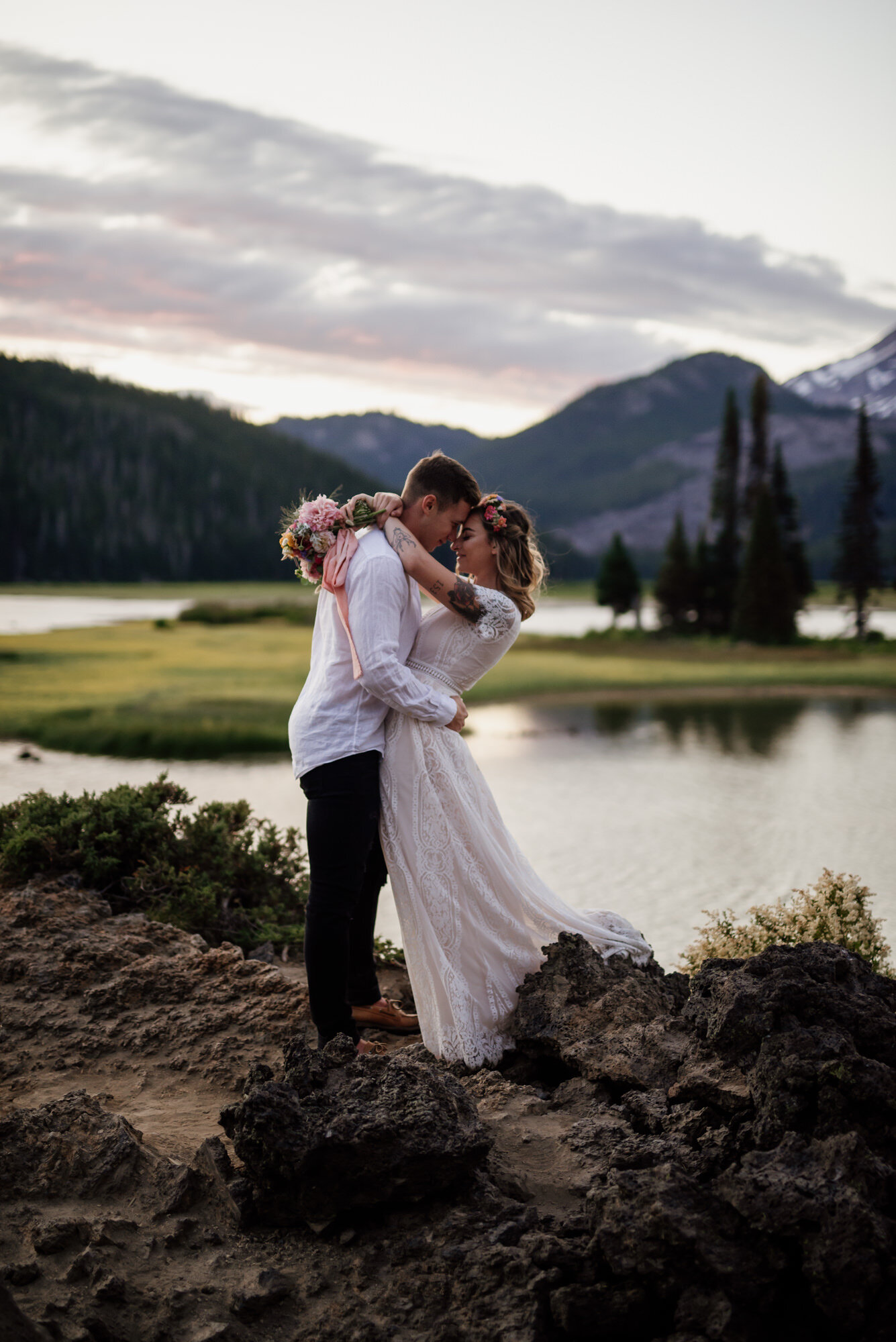 Eloping couple embrace at sunset in front of a calm lake.