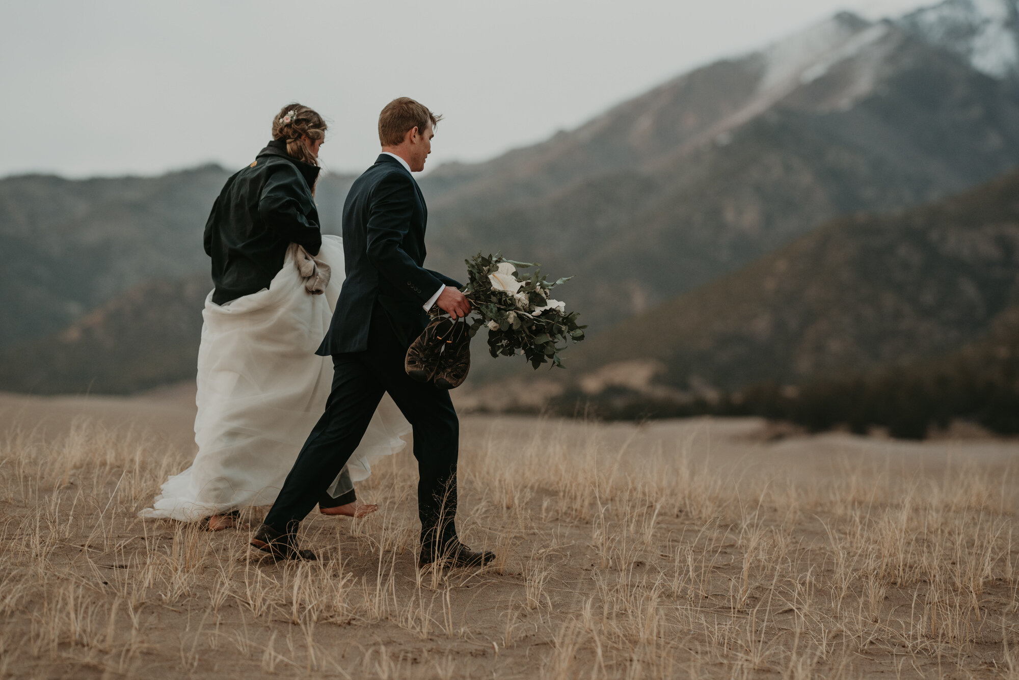 A barefoot couple walk through sand dunes on their wedding day.