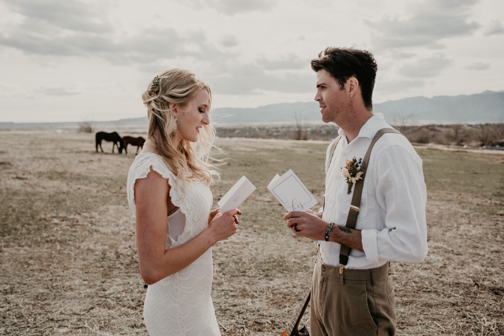 A couple ecxhanges vows while horses graze in the distance.