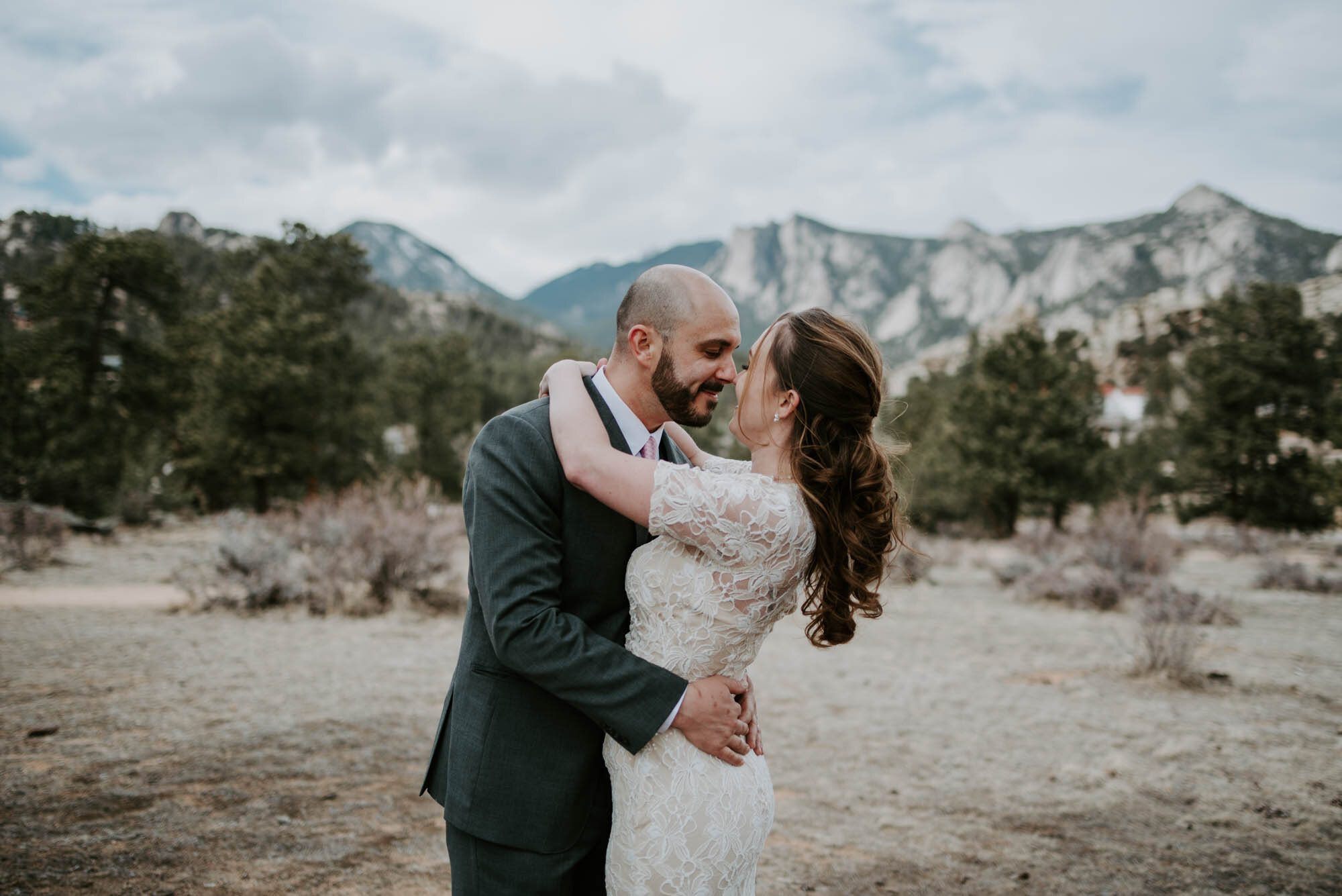 A newly married couple embrace in front of mountains in Estes Park, Colorado.