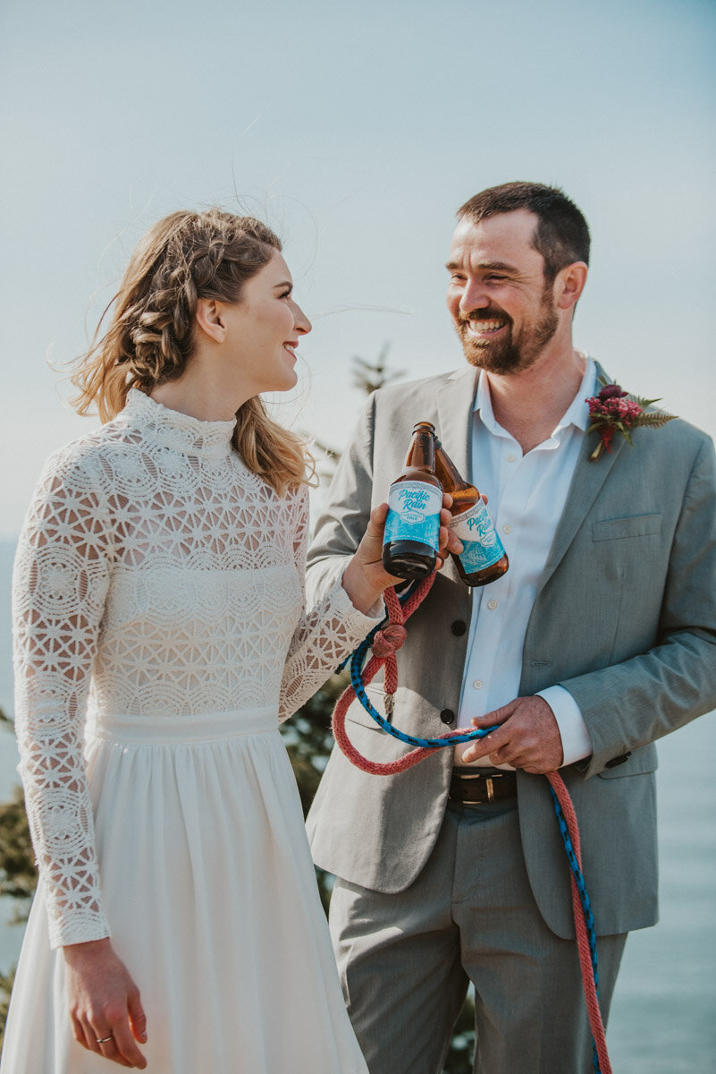A couple toasts with bottles of beer on their wedding day.