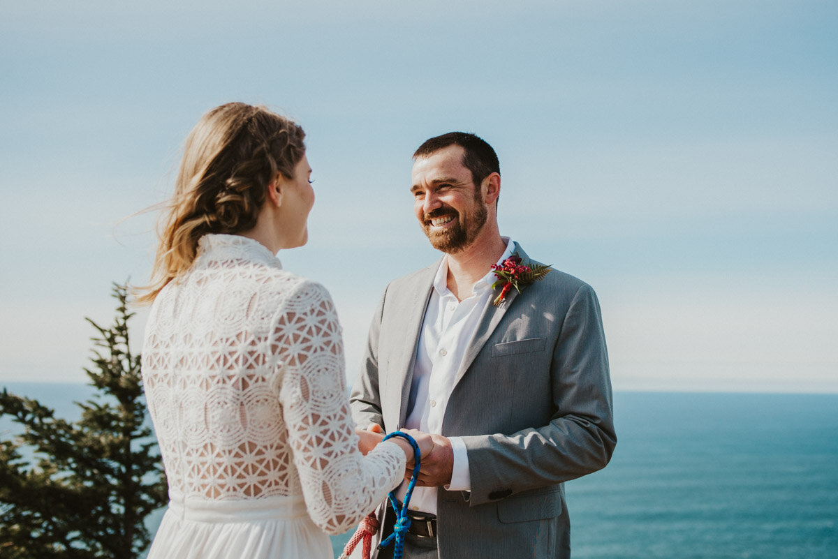 A couple exchanges marriage vows overlooking the ocean.