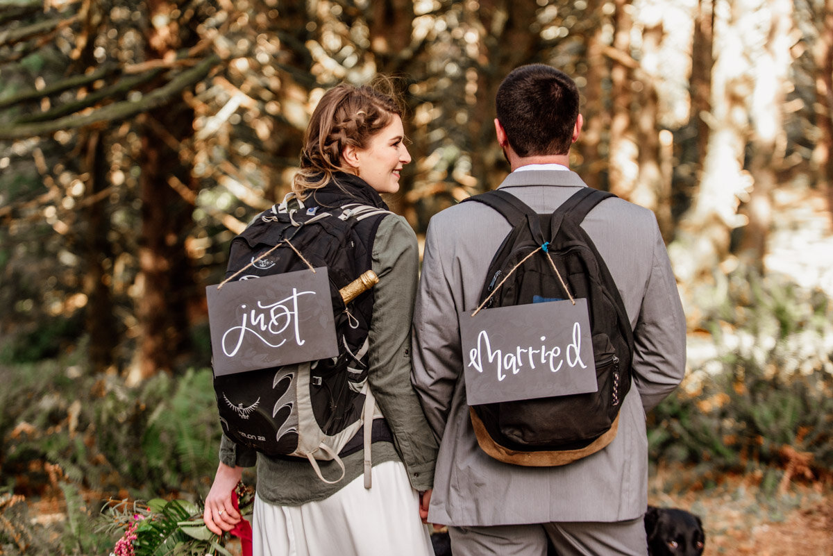 """A couple shows off signs that say """"Just Married"""" which hang from their backpacks."""