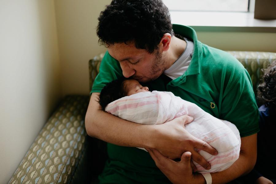 dad kissing newborn baby girl