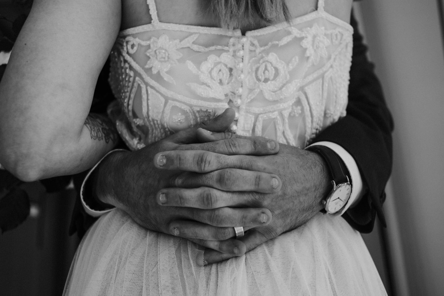 groom wrapping arms around brides waist