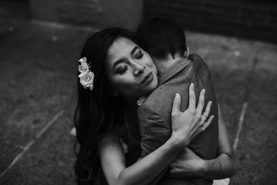bride hugging son on sidewalk