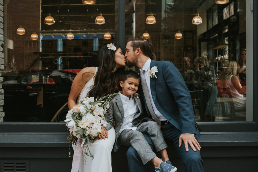 bride and groom kissing over son