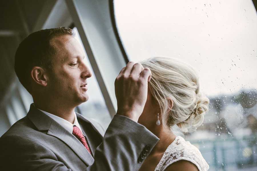 groom brushing brides hair from face