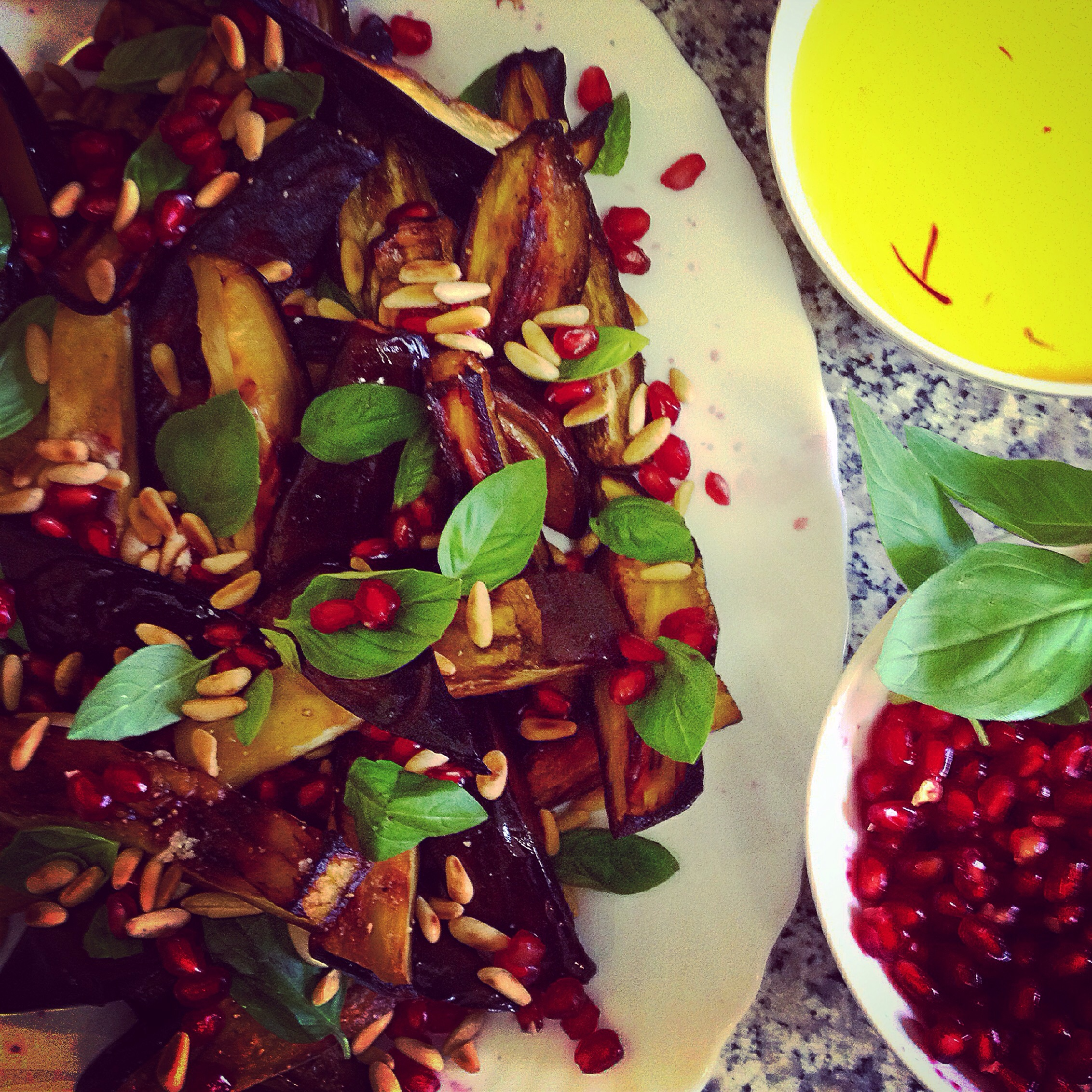 Gebackene Auberginen mit Basilikum, Granatapfel und Pinienkerne an einer Joghurt-Safran Sauce