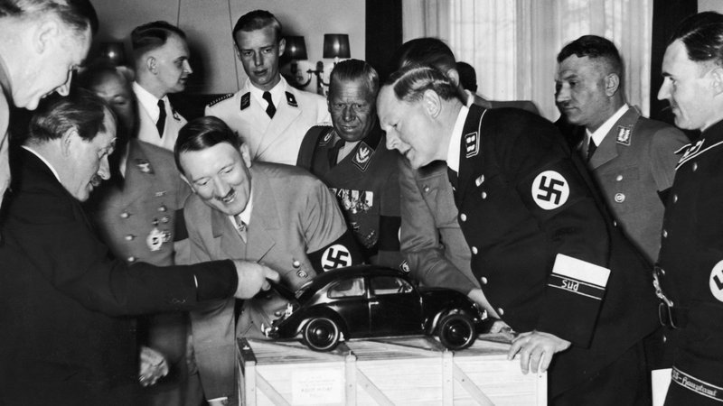 Ferdynand Porshe (z lewej), Adolf Hitler i konstruktorzy podczas omawiania prototypu samochodu