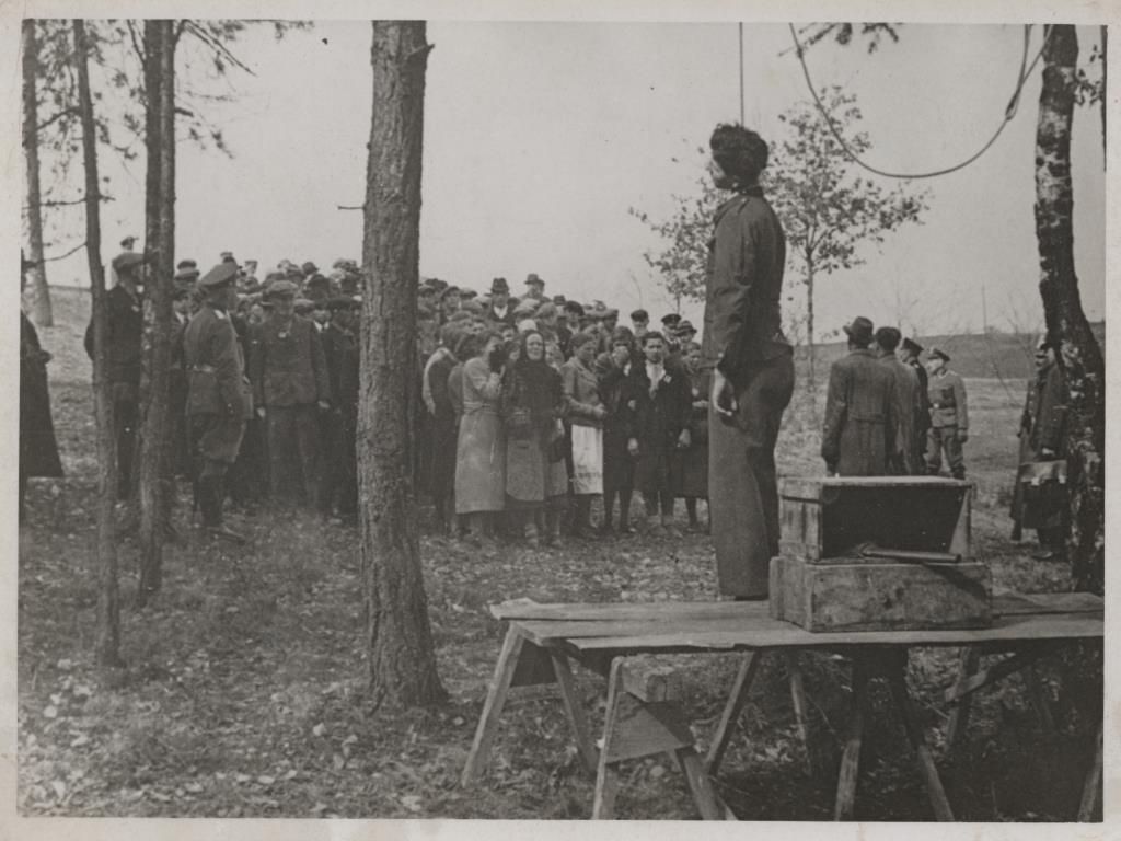 Powieszenie polskiego robotnika przymusowego Juliana Majki. Na miejsce egzekucji Juliana Majki sprowadzono Polaków, którzy pracowali w tej okolicy. Funkcjonariusz Gestapo upomniał ich przy okazji, by nie łamali niemieckich przepisów. Michelsneukirchen (Bawaria), 18 kwietnia 1941 r. Źródło: Zbiory Vernona Schmidta, weterana 90. Dywizji Piechoty Armii Stanów Zjednoczonych, Fresno