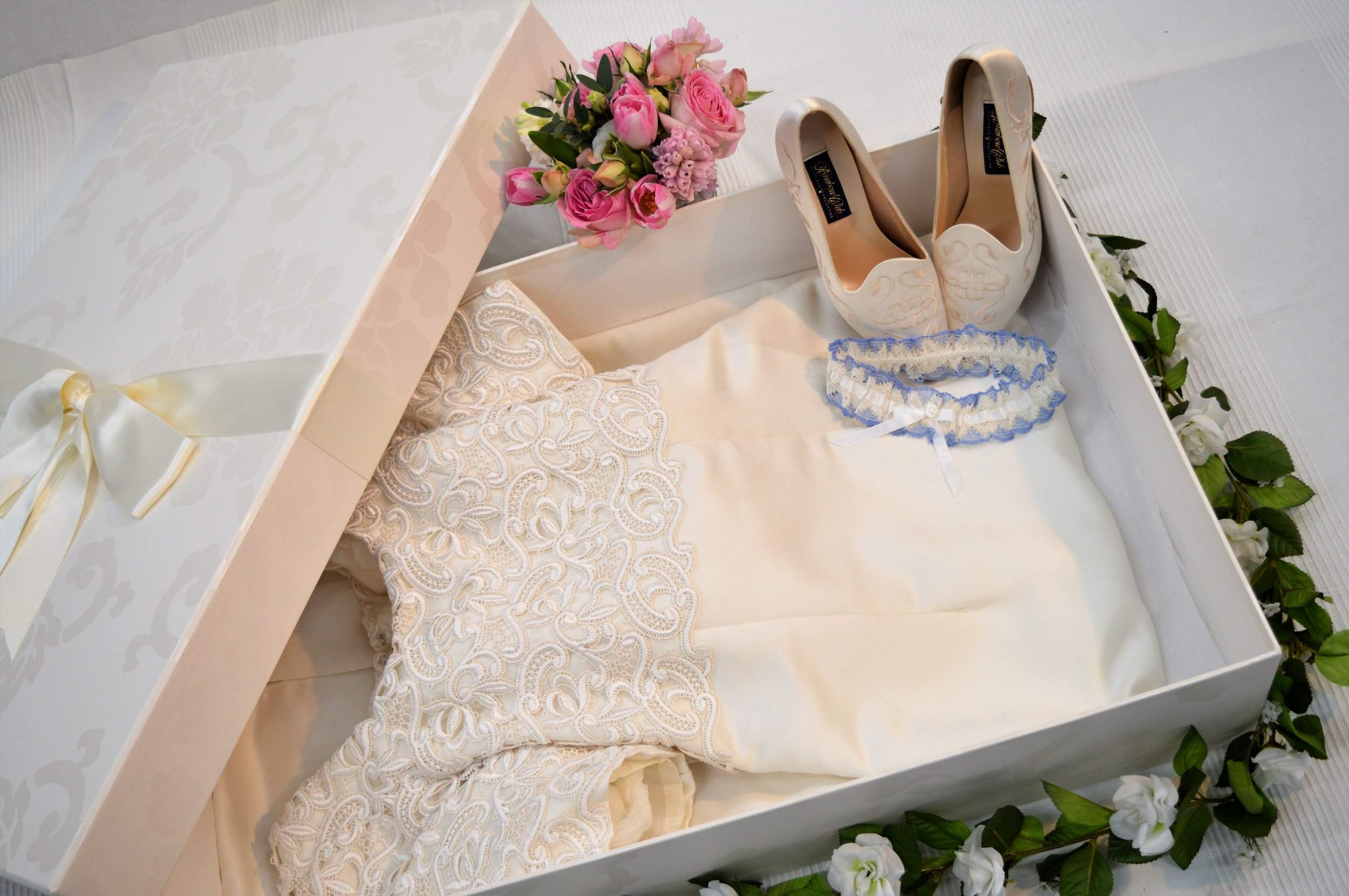 A wedding dress with shoes and garter.