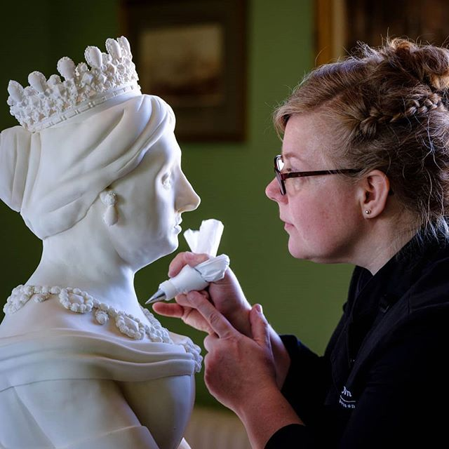 "Victoria.  What an honour to get to create our very first person-shaped cake sculpture for Osborne House's 200th anniversary of Queen Victoria's birth.  Full sized (at 4ft 10"") she was sculpted out of Victoria sponge with Cornish strawberry jam and creamy vanilla buttercream. The cake was covered with white chocolate ganache and white sugar paste, then very gently airbrushed in warm white tones with touches of grey.  Her crown, earrings, necklace and broach were based on the Emerald suite, given to Queen Victoria by her husband Prince Albert in 1846. This was the year after he bought Osborne House for her, where Victoria preferred to spend all her birthdays. . . . #victoria #queenvictoria #youngvictoria #victorian #osbornehouse #isleofwight #southcoast #historyinthemaking #luxury #cake #cakesculpture #artist #wondermaker @itv #victoriasponge #daisygoodwin #jennacoleman #christinejensen #masterpiecetheatre @WGBH @mammothscreen #pastrychef #cornwall #london #peboryon #extremecakemakers @englishheritage"
