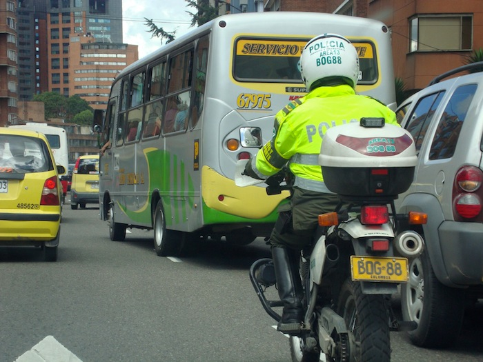 We follow a police officer weaving through Bogota traffic on his motorcycle.
