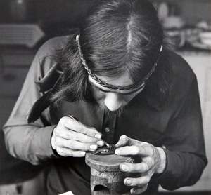 "George Yeltatzie in 1975. Copyright Ulli Steltzer. Source: University of Victoria: ""Black and white photograph of George Yeltatzie carving a small argillite pendant on a raised mount. Only his upper torso is in view. He is look downward at the carving so that the top of his head is in view. In one hand, he is holding the carving upon a pedestal on a table and carving with a blade in his right hand."""
