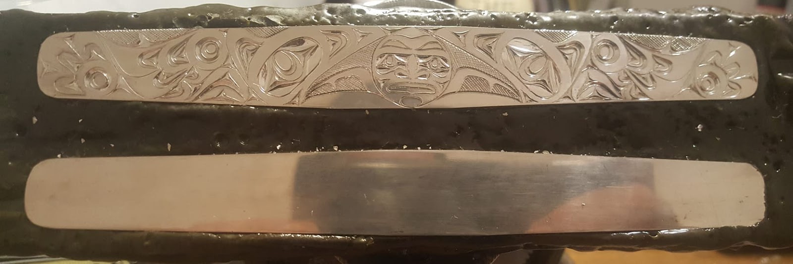 This beautiful work in progress was created by the well known Haida artist James Sawyer. It is 2 inches wide by 7 inches long and features two ravens stealing the moon and is carved in sterling silver.