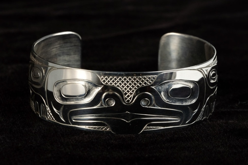 This sterling silver frog bracelet was carved by Haida carver, Derek White, who is from Old Massett, Haida Gwaii. This bracelet measures 3/4 inch wide and 6 1/4 inches long.