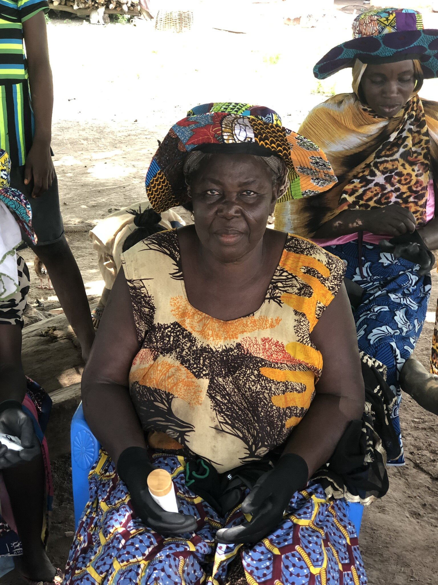 A shea tree farmer in Ghana sits in a chair with her new sun hat and rubber gloves