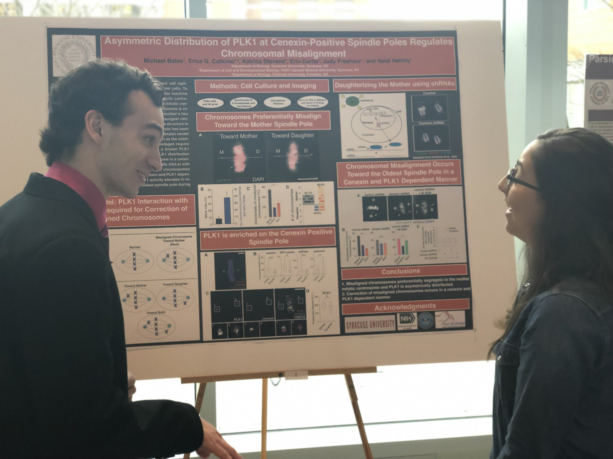 Michael presenting his poster to a Hehnly Lab Alum, Alice. This work was done in collaboration with Erica Colicino (Hehnly Lab, currently at University of Michigan).
