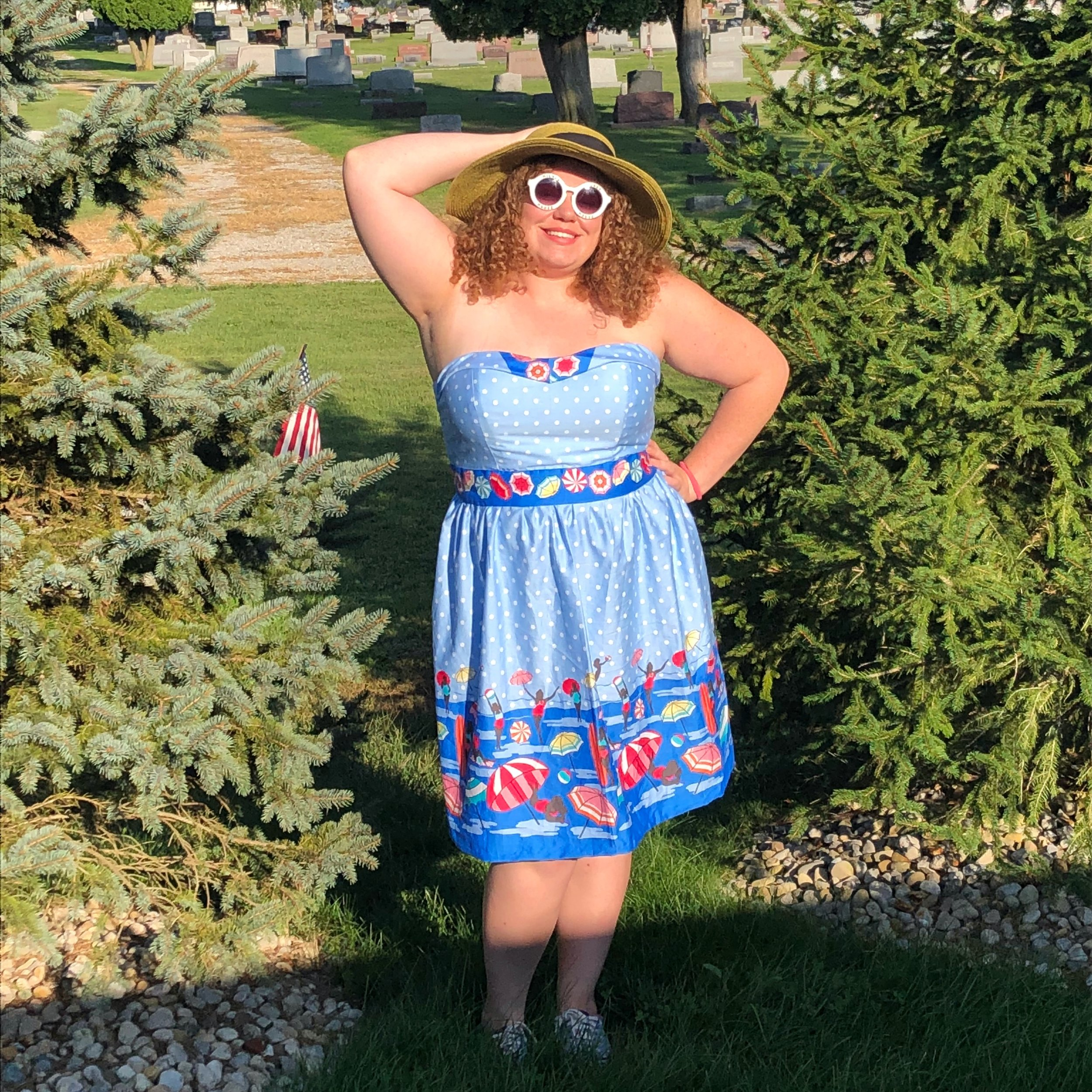Woman with curly auburn hair standing outside with a sun hat and sunglasses on wearing a blue polka dot dress with pinups in swimsuits printed on it