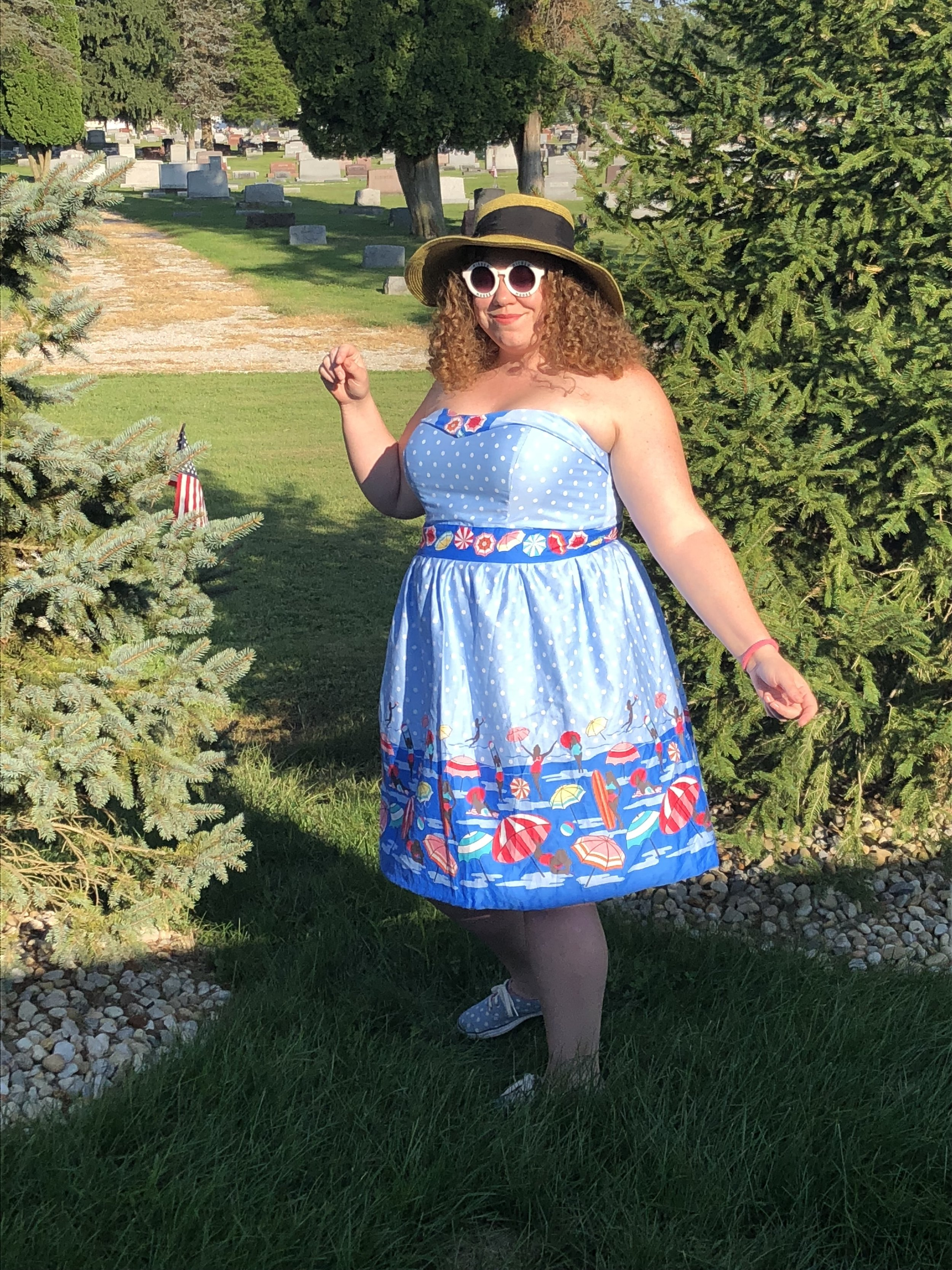 Woman with curly auburn hair standing outside with a sun hat and sunglasses on wearing a blue polka dot dress with pinups in swimsuits printed on it. A cemetery lies behind her.