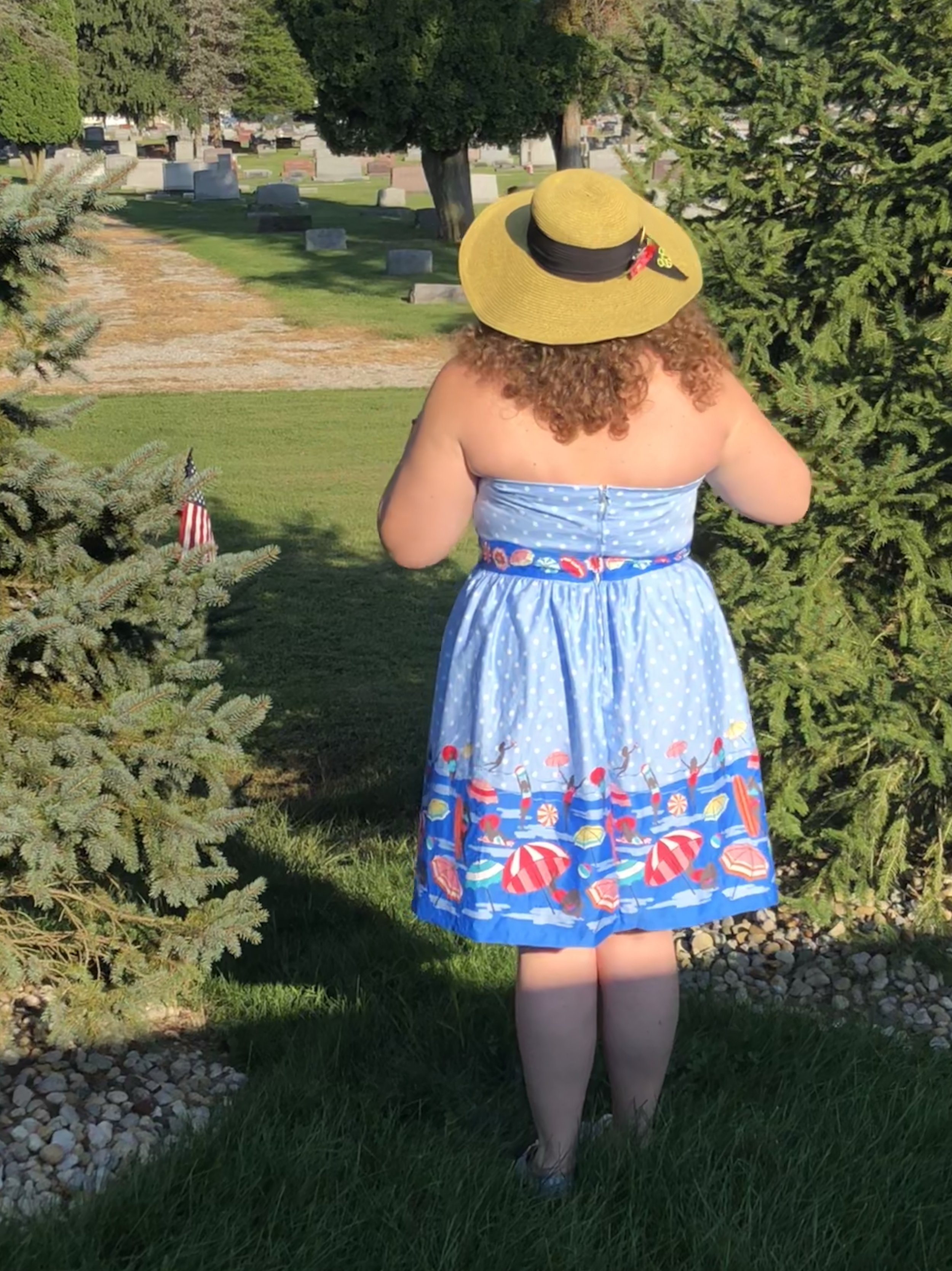 A woman with curly auburn hair wearing a sun hat, and a blue polka dotted dress with pin ups at the beach printed on it. A cemetery lies behind her.