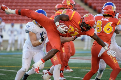 Calgary Dinos running back Jeshrun Antwi goes airborne during a 4th quarter carry in the Hardy Cup. The Dinos downed the Thunderbirds 46-43 at McMahon Stadium in Calgary on Saturday November 12, 2016.- Maxwell Mawji, Capture Candy.