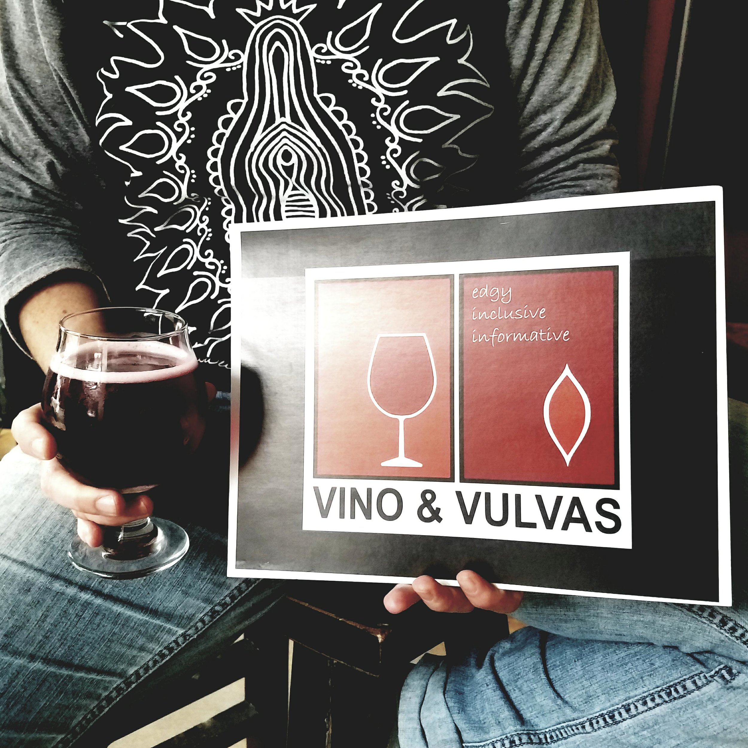 Image of person in jeans and vulva art t-shirt sitting on a stool holding a Vino & Vulvas sign along with a glass of dark cider.