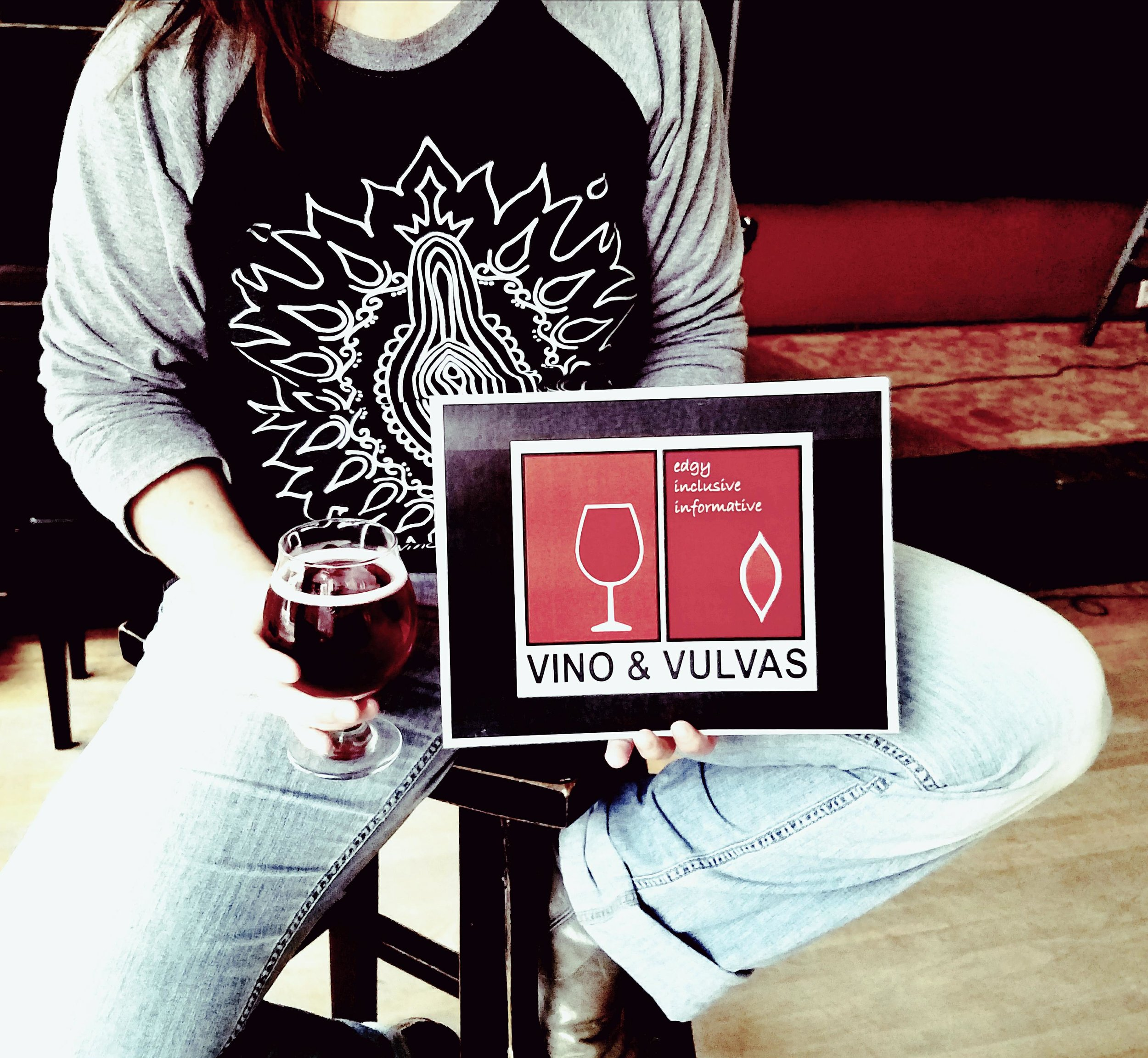 Image of person sitting on bar stool holding a photo of the Vino & Vulvas logo and a glass of cider.