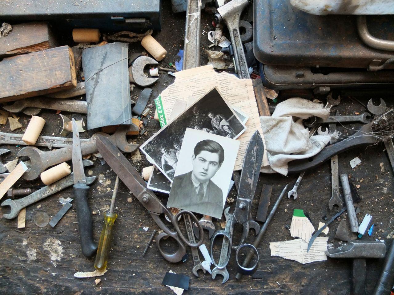 Retrat d'un dels protagonistes del llibre damunt l'antiga taula de treball del seu taller mecànic.
