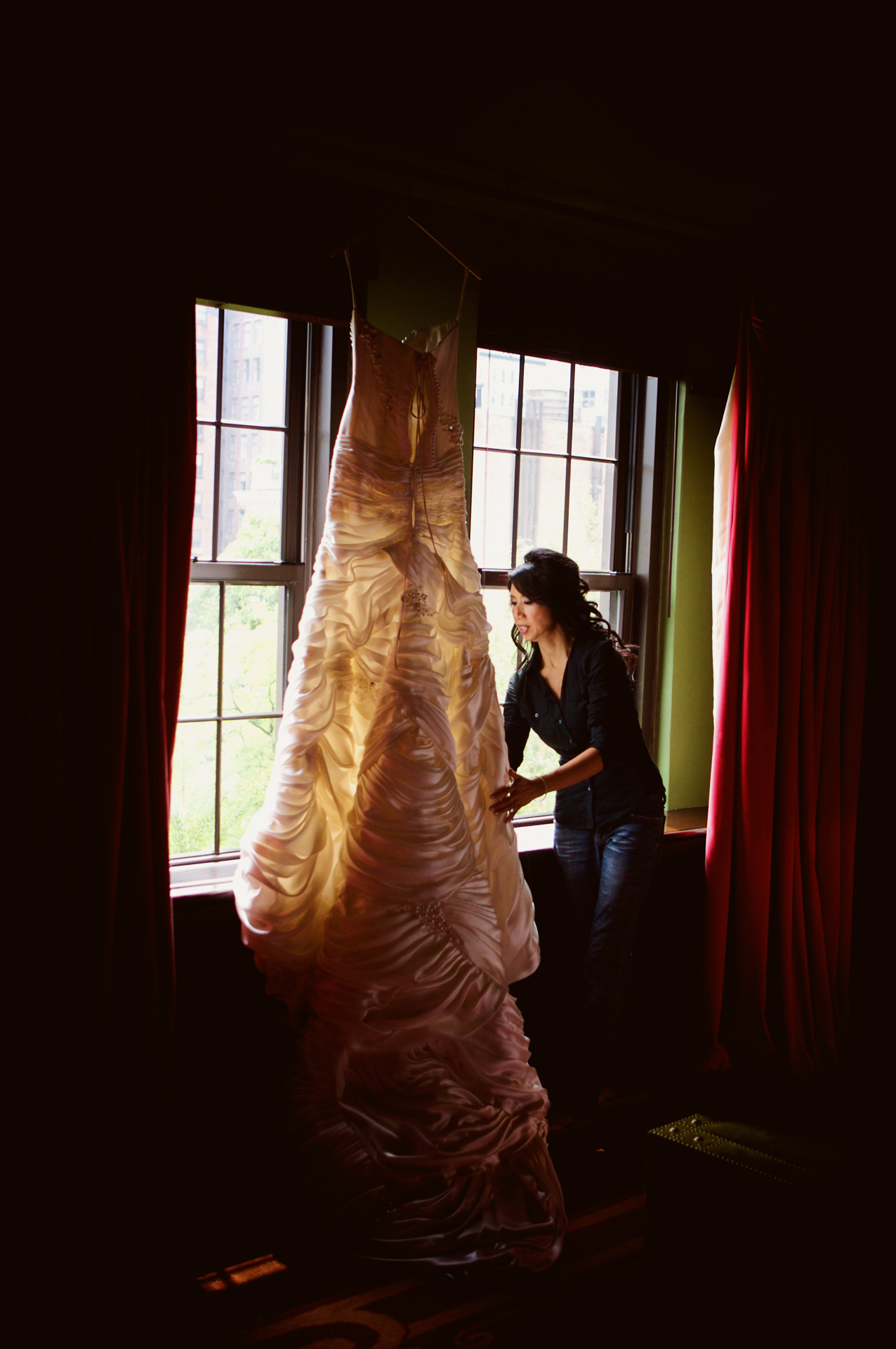The brides mother hangs the dress in the window as the bride gets ready for her wedding at Angel Orensanz in NYC.