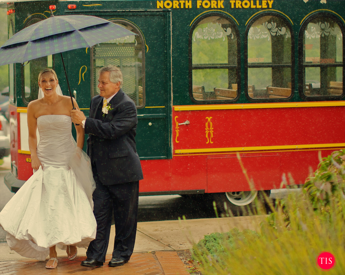 The father of the bride walks with her towards a church in The Hamptons in the pre-hurricane rain. Moment captured by  Maring Visuals  .