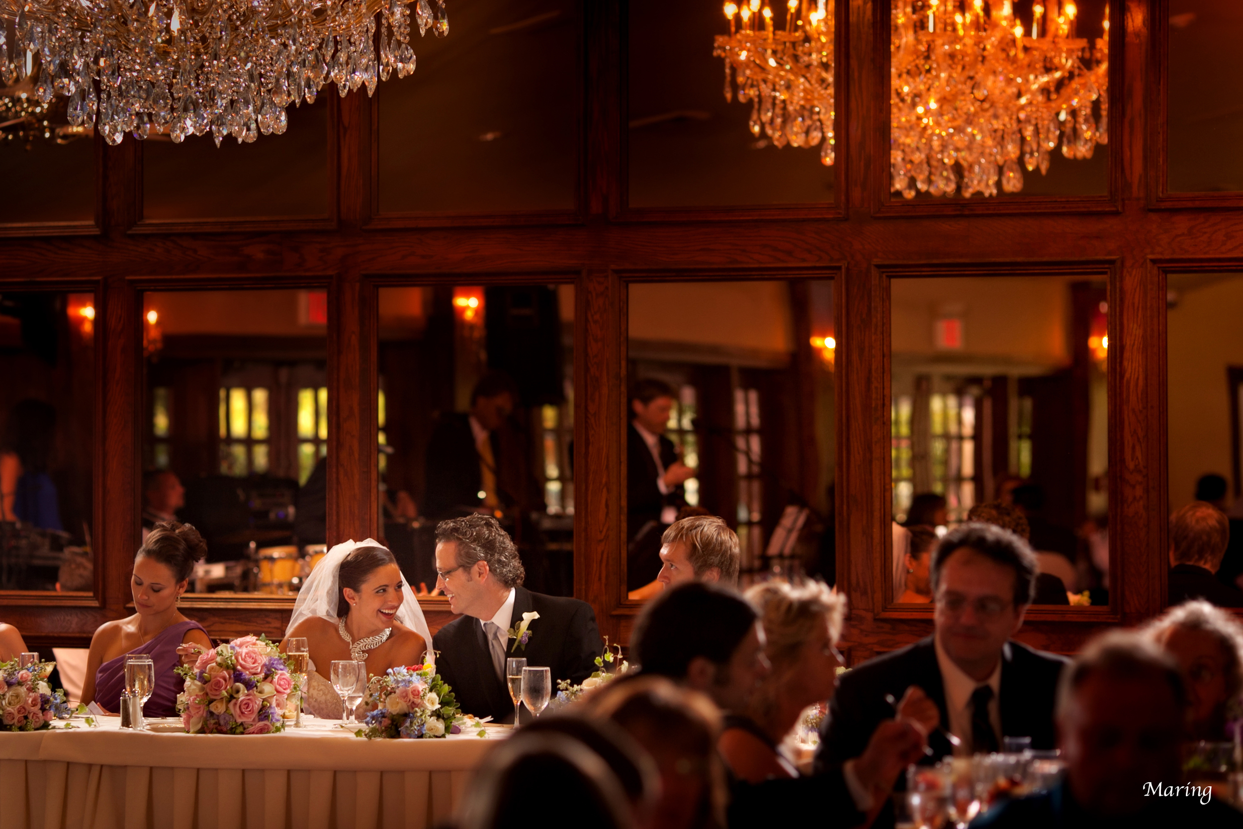A bride and groom dine together at their head table making sure to eat before greeting tables.