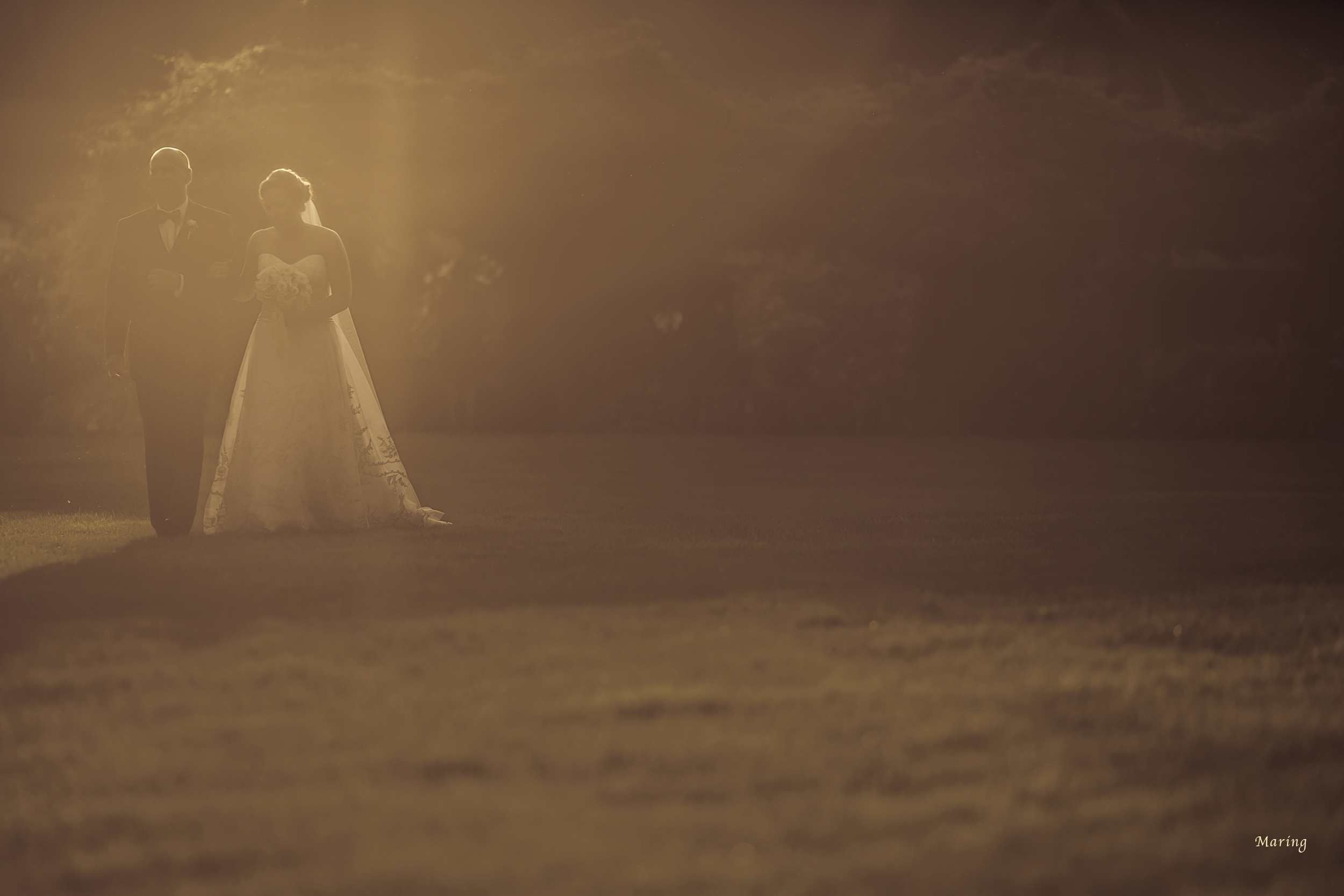 Gorgeous and creative light flares into the lens creating a remarkable photograph of the bride and her father walking towards the  wedding ceremony at Saint Clements Castle  in Connecticut. Photographer Jennifer Maring allowed the sun to flare into the lens to create this lovely fine art glow.
